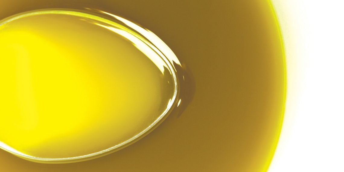 Spoon under extra virgin olive oil
